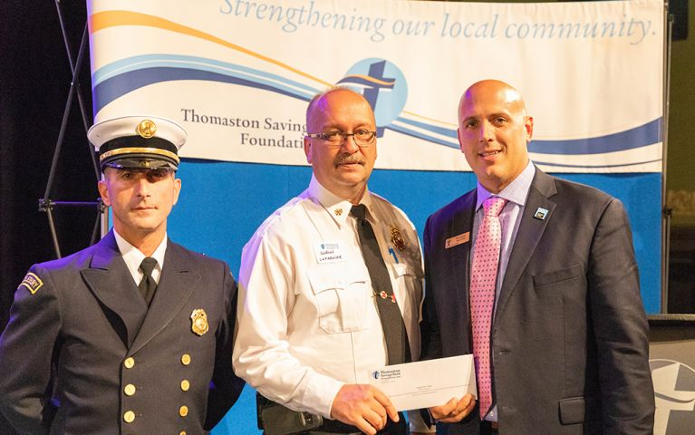 A police officer and two men smiling for a picture with a check at the 2018 TSB Foundation Night