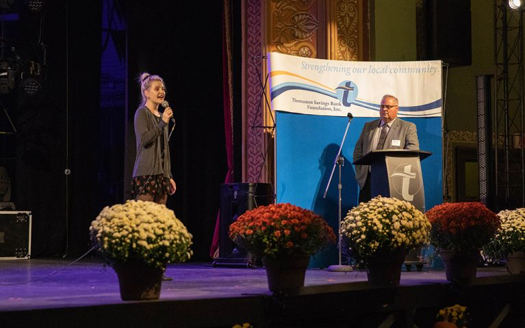 A man at the podium and a woman with the microphone on stage at the 2018 TSB Foundation Night