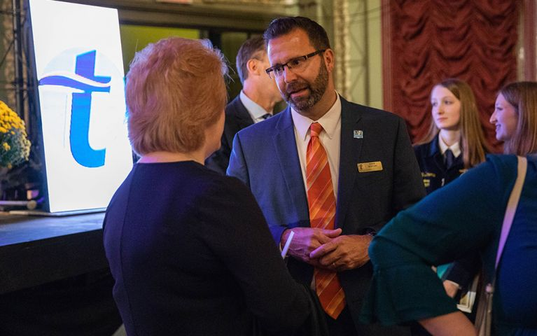 A man and woman having a conversation at the 2018 Thomaston Savings Bank Foundation Night