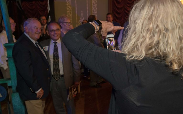 Female attendee is captured taking a photo of two smiling male attendees at Foundation Night 2019.