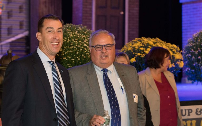 Thomaston Savings Bank CEO and president, Stephen L. Lewis and male attendee smile and pose.