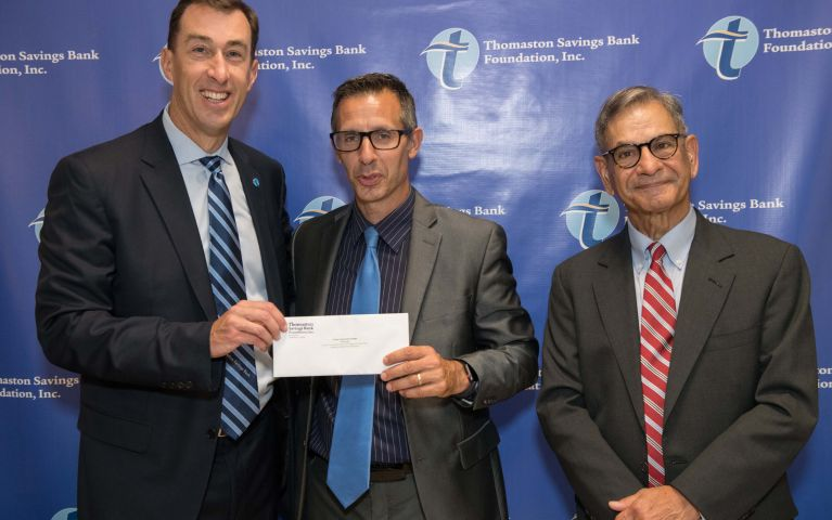 Stephen L. Lewis, President and CEO of Thomaston Savings Bank poses and smiles while presenting a check to two loyal men at the 2019 TSB Foundation Night.