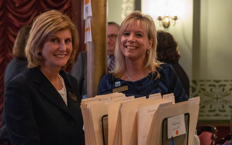 Two women smiling for a picture with filing folders on a table in front of them at the 2018 TSB Foundation Night