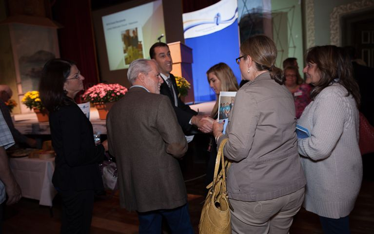 President of Thomaston Savings Bank, Stephen L. Lewis, shaking hands with a woman in a group at the 2017 TSB Foundation Night