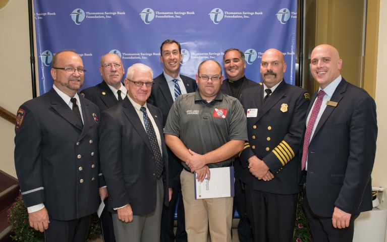 Seven Connecticut first responders pose in uniform with TSB CEO during 2019 Foundation Night event.