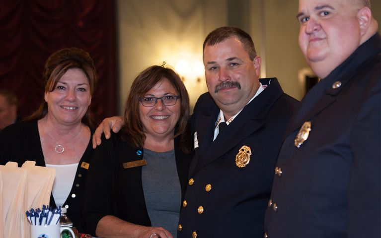 Two men in uniform and two women smile together for a picture at the 2017 TSB Foundation Night