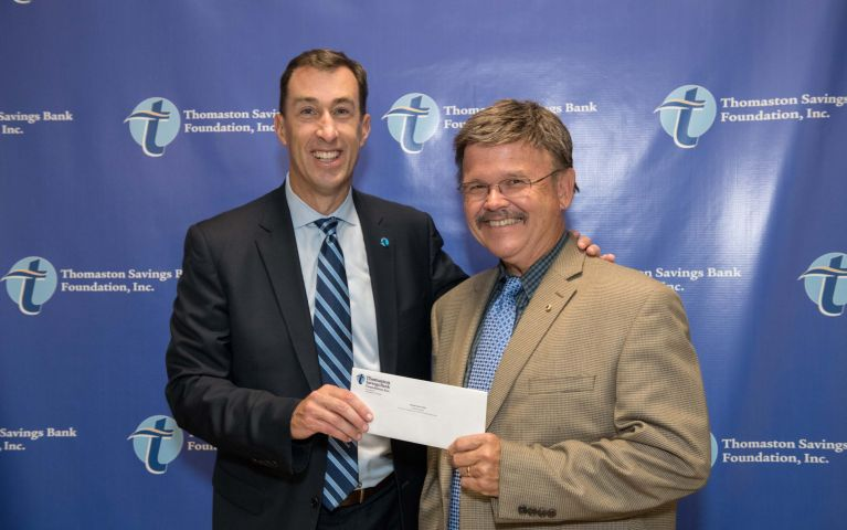 Stephen L. Lewis, President and CEO of Thomaston Savings Bank happily presents an envelope to a community member at the 2019 TSB Foundation Night.