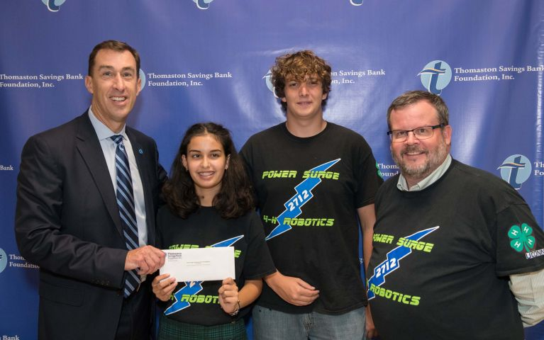 Thomaston Savings Bank President and CEO, Stephen L. Lewis presenting a check to Power Surge, FRC team # 2712, a new 4-H sponsored FIRST Robotics Competition team at the 2019 Foundation Night.