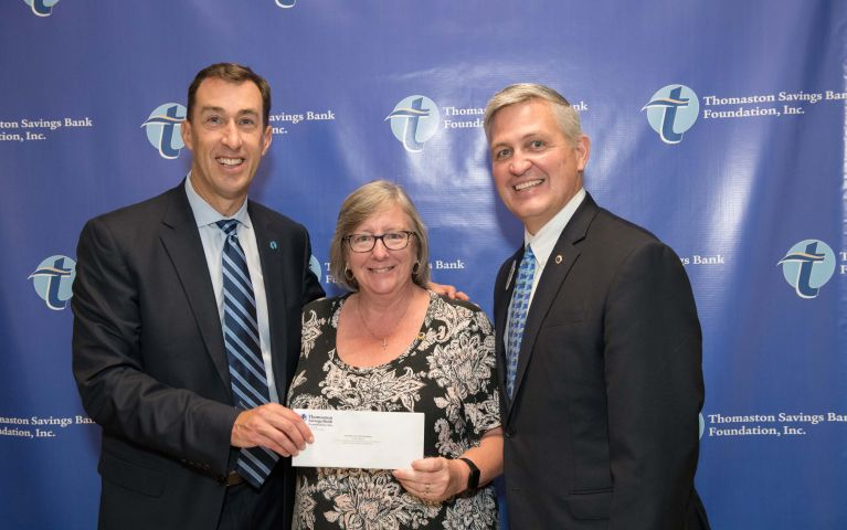 Stephen  L. Lewis, CEO and President of Thomaston Savings Bank, smiles next to TSB customer while presenting her an envelope at the 2019 Foundation Night.