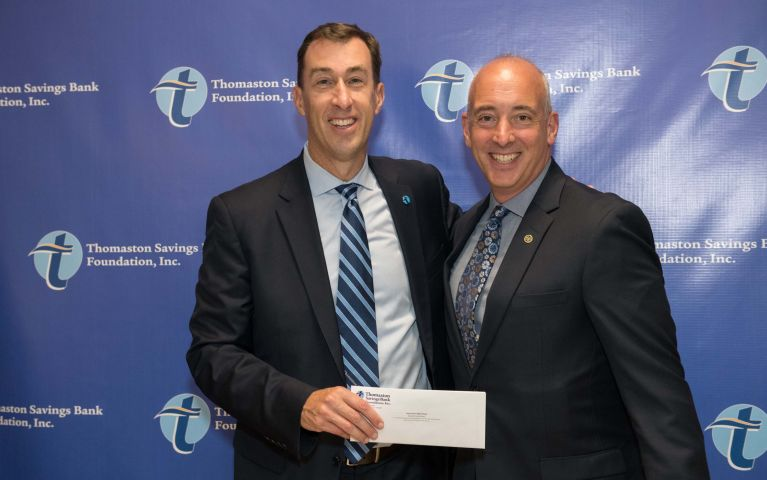 CEO and President of Thomaston Savings Bank, Stephen L. Lewis, happily smiles next to TSB customer while presenting him at the 2019 Foundation Night with an envelope..