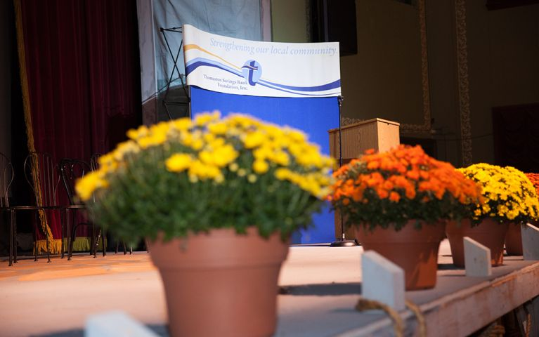 Picture of the podium with yellow and orange flowers lining the stage at the 2017 TSB Foundation Night