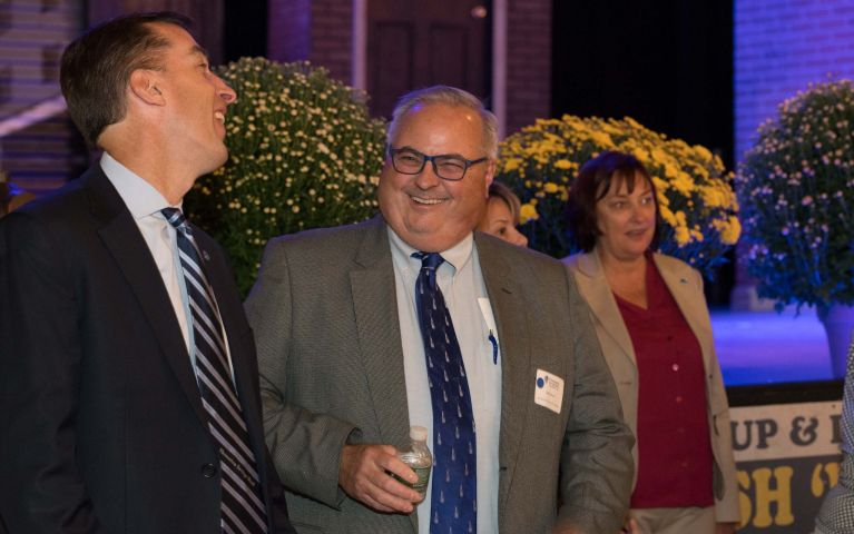 Thomaston Savings Bank CEO and president, Stephen L. Lewis, laughs with male attendee.