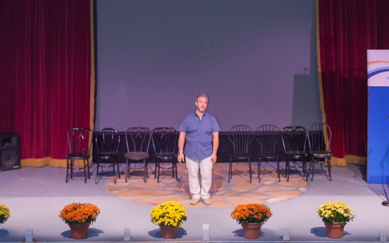 A man standing in front of chairs onstage at the 2017 TSB Foundation Night