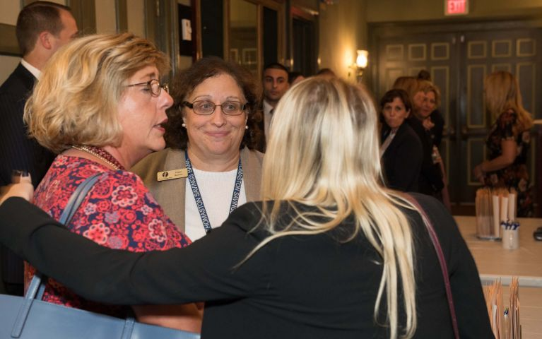 Female Thomaston Saving Bank members and attendees converse with eachother in theater where 2019 Foundation Night is held.