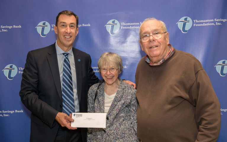 CEO and President of Thomaston Savings Bank smiles with two elderly TSB customers and presenting them an envelope at the 2019 Foundation Night.