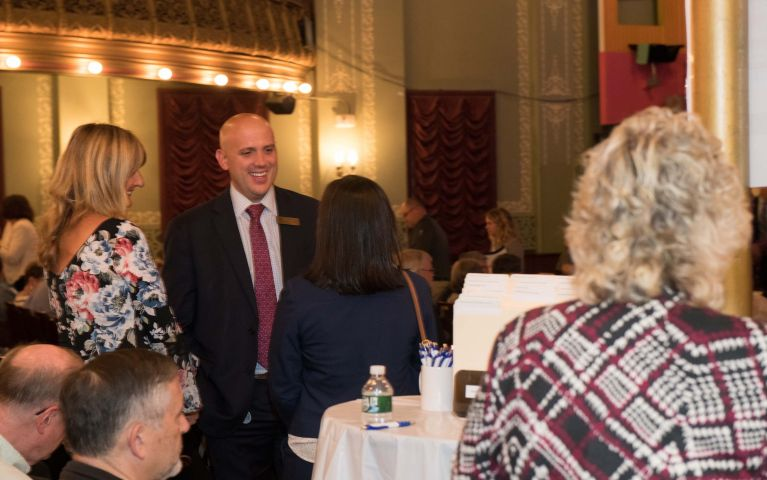 Male TSB member smiles at another attendee while engaging in conversation at Foundation Night 2019.