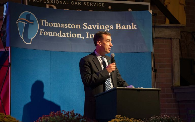 CEO and president, Stephen L. Lewis stands behind podium with microphone in front of TSB banner to speak to the crowd.