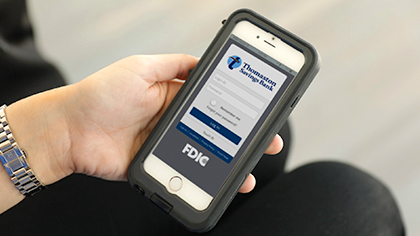 Hand holding phone with Thomaston Savings Bank mobile app displayed
